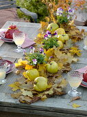 Table decoration with quinces on a carpet of foliage