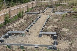 Flowerbeds edged with metal frames on dot foundations
