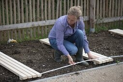 Woman measuring distances of wooden grates in flower beds