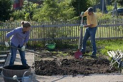 Woman and man cleaning flower beds for the new plant
