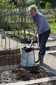Woman removing potting soil to improve the soil in the bed