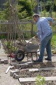 Man puts rounding of bed frame of granite stones