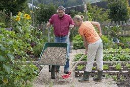 Man tilting wheelbarrow with gravel, woman spreading it with shovel