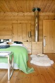 Stainless steel oven pipe, white sheepskin rug and bed in comfortable dacha bedroom