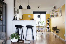 Open-plan kitchen-dining room with yellow wall