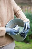 Woman holding zinc bucket of granules