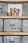 Recycled tin cans, knitted cords and retro metal storage boxes on open-fronted shelves