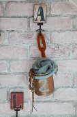 Feminine accessories in painted tin can with knitted cords hung on brick wall