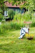 Schaukelstuhl mit umhäkelter Decke und Kissen auf der Wiese