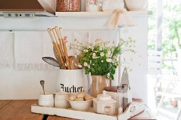 Kitchen utensils, sugar bowls and vase of flowers on white wooden tray