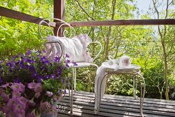 Vintage-style crockery on ornate metal table and cushion on chair on wooden deck