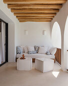 Sofa and pouffes in Mediterranean loggia with arcades