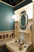 Sink below designer mirror in bathroom