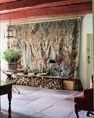17th century Flemish tapestry and firewood stacked under bench in foyer