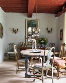 Wooden table, 18th-century Swedish chairs and French mirror above antique sideboard