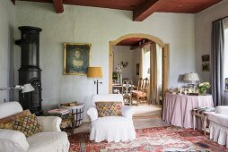 Round iron stove, loose-covered armchairs and Heriz rug
