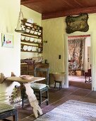 Plate rack, wooden table and antique picture in vintage kitchen