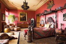 Ornate carved bed in red bedroom with gilt-framed oil painting