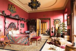 Ornate carved bed in red bedroom with tiger-skin rug