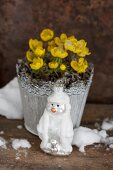 Pot of winter aconites and snowman Christmas tree bauble