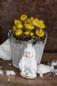 Winterlinge im Blumentopf davor Baumanhänger in Schneemannform