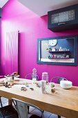 Baking utensils on wooden table in front of black-framed mirror on magenta wall
