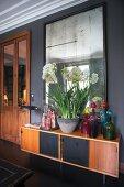 Retro Sideboard mit bunten Glasflaschen und Pflanzschale mit weißen Blüten vor Wandspiegel
