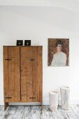 Painting of woman and candles in hollow tree trunks next to rustic wooden cupboard