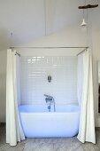 Blau beleuchtete weiße Badewanne mit Duschvorhang in modernisiertem Altbau