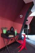 Schwarzer Retro Schreibtisch und roter Holzstuhl in Dachzimmer