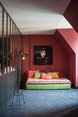 Bett mit verschiedenen Matratzen und Kissen vor mauvefarbener Wand mit Frauenfotografie