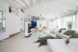 Edler Wohnbereich mit weißer Couch, Bogenleuchte und Zebrafell