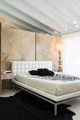 Schlafzimmer mit antiker Tischleuchte und Doppelbett mit weißem Leder vor Naturstein-Raumteilerwand