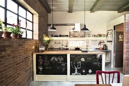 Sideboad with chalkboard back wall in open-plan kitchen
