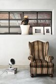 Upholstered wingback chair on concrete floor below industrial window