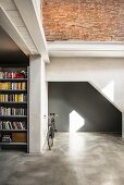Grey niche, bicycle and bookcase in converted loft apartment