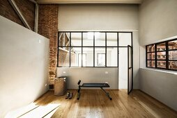 Black exercise bench in home gym with industrial glazing and oak parquet floor
