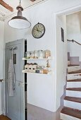 Staircase next to kitchen shelves and grey wooden door in country house