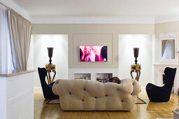 Designer seating in front of urns on tables in niches with indirect lighting in elegant living room