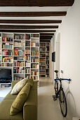 Bicycle behind sofa in living room with large bookcase