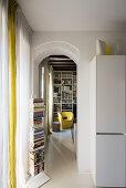 Vertical bookshelf next to doorway leading into living room