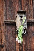 White tulips tied to weathered nesting box