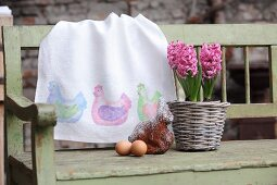 Hand-made table runner with pattern of hens, potted hyacinths, cake and eggs on wooden bench