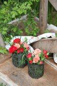 Posies of carnations in metal vases