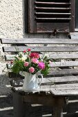 Posies of carnations in jug on weathered garden bench