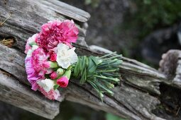 Bouquet of carnations tied with grasses on weathered wood