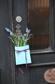 Paper bag of grape hyacinths and rosemary hung on door