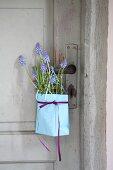 Papiertüte mit Traubenhyazinthen und Rosmarin hängt an der Tür