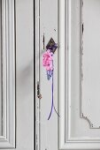 Grape hyacinth and two pink hyacinth florets hung from wardrobe key