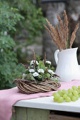 Wreath decorated with white asters and poppy seedheads next to grasses in jug on garden table